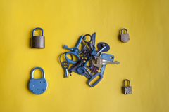 Bunch of keys and locks. Many keys and locks lie on a yellow background Royalty Free Stock Images