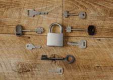 Many keys one lock. A lot of metal keys and a steel lock on a wooden boards stock image