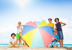 Many kids in large group behind beach umbrella Stock Photography