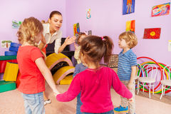 Many kids clap hands with teacher in kindergarten. Group of kids boys and girls hold stand together and clapping hands with teacher showing and giving Royalty Free Stock Photo