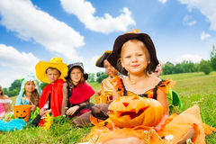Many kids in Halloween costumes sitting close. Many kids in Halloween costumes sit close on the grass with girl in hat holding Halloween pumpkin royalty free stock photo