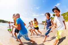 Many kids having fun racing on the sunny beach. Fish-eye lens portrait of group of age-diverse kids running on sandy sunny beach Stock Image