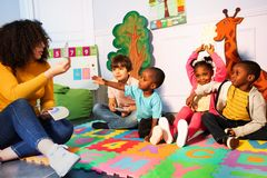 Many kids in kindergarten play games with teacher royalty free stock photography