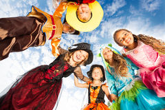 Many kids look down in circle wearing costumes Stock Photos
