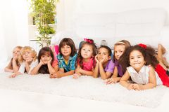 Many kids in a row on the floor at home Stock Photos
