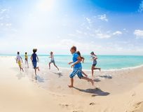 View from behind of kids run on the sea beach Royalty Free Stock Image