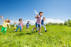 Many kids running and boy holding airplane toy. Many kids running and boy holding white airplane toy in the field during summer sunny day Stock Photo
