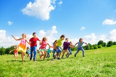 Many kids running in the field Stock Images