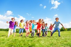 Many kids running. Large group of kids, friends boys and girls running in the park on sunny summer day in casual clothes Stock Image