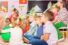 Many kids sit in developmental kindergarten class. Many kids boys and girls sit in developmental kindergarten class together wearing handmade headwear Royalty Free Stock Image