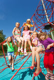 Many kids sit on red ropes of playground Royalty Free Stock Images