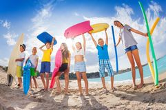 Many kids on a beach with swimming tools and toys Stock Images