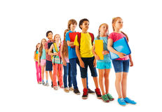 Many kids standing in line with books Stock Photos