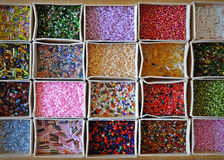 Many kinds of beads of different colors and shapes. Many kinds of beads of different colors and shapes in cardboard boxes. Background, top view Stock Images