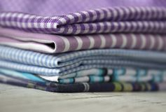 Many kinds of cotton fabrics in stripes and cage on a lilac background. Purple, blue and turquoise fabrics for sewing stock photos
