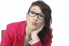 Many kisses for you. Girl with glasses wearing red jacket blows a kiss Royalty Free Stock Photography