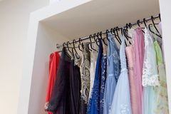 Evening long dresses on hanger in the dress rent shop for the wedding day or photo session. Selective focus. Ball gown stock image
