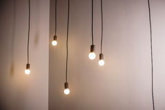 Many lamps on a long cord and hanging light in the room.  Royalty Free Stock Image