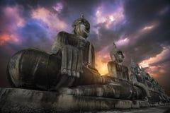 Many large Buddha images and  orange skies At Thung Yai District stock photo