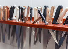 Many large knife hanging wooden storage  in the kitchen of restaurant Royalty Free Stock Images