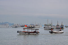 Many Large Tourist Junk Boats without sail scattered at Halong Bay off Bai Chay Tourist Wharf Stock Photo