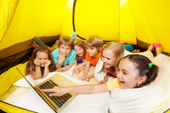 Many laughing with laptop children in a tent Stock Photo