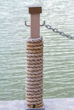 Many layers of rope tied around a wooden log, in the shade on a Royalty Free Stock Images
