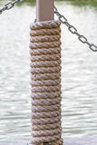 Many layers of rope tied around a wooden log, in the shade on a Royalty Free Stock Photo
