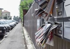 Many leaflets in mailbox. Many advertising leaflets are hanging from an overloaded letterbox Royalty Free Stock Photography