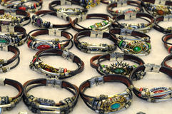 Many leather bracelets on display. A photo taken on numerous leather bracelets with bold ornaments on display stock images