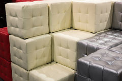 Many leather footstools of different colors in  stack Stock Photography