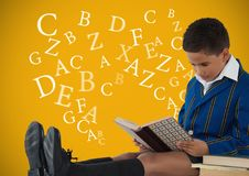 Many letters around Boy reading in front of yellow background. Digital composite of Many letters around Boy reading in front of yellow background Royalty Free Stock Photo