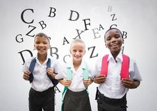 Many letters around School kids in front of grey background. Digital composite of Many letters around School kids in front of grey background Stock Photo