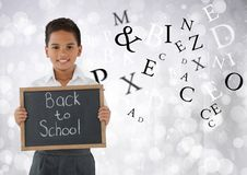 Many letters around Schoolboy holding back to school blackboard in front of bright bokeh background. Digital composite of Many letters around Schoolboy holding Stock Photo