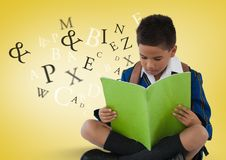 Many letters around Schoolboy reading in front of yellow background. Digital composite of Many letters around Schoolboy reading in front of yellow background Stock Photo