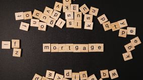 Many letters sets up a word `Mortgage` on a black table Stock Photography