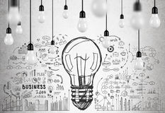 Many light bulbs and business idea. Large light bulb sketch is surrounded by smaller business icons drawn on a concrete wall. There are light bulbs hanging on Royalty Free Stock Photos