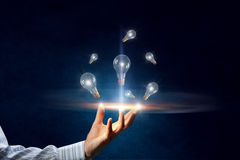 Many light bulbs in palm . Mixed media Stock Images