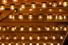 Many light bulbs shining bright. Plenty lightbulbs in rows on ceiling burn Royalty Free Stock Photo