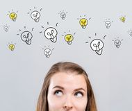 Many light bulbs with young woman. Looking upwards royalty free stock images