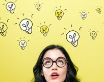 Many light bulbs with young woman stock photos