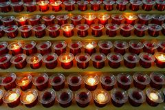 Many lighted candles in candlesticks. Sacred light. Burning candles in church. Concept of religion. Bright yellow light in the evening, close-up royalty free stock photos