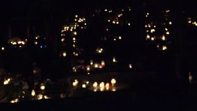 Many lighted religion candle on tomb in cemetery evening. 4K stock footage
