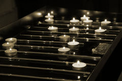 Many lit candles in church. Many lit candles on a dark background in church (background Stock Image