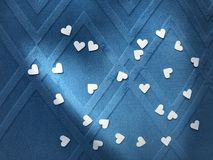 Many of little heart shape white papers on square pattern blue fabric royalty free stock photos