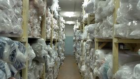 Many long shelves with rolls of fabrics in stock slow motion. 4k stock footage