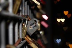 Love locks on a bridge rail with beautiful heart shaped bokeh royalty free stock images