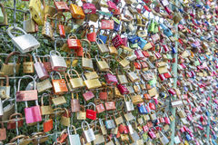 Many love padlocks locked on iron chain at landmark. Stock Photos
