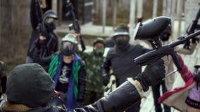 Many mans in paintball mask lift up closeup gun, begin aggressive 4K strike.