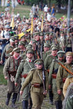 Many mar�hing Russian soldiers-reenactors. Royalty Free Stock Photography